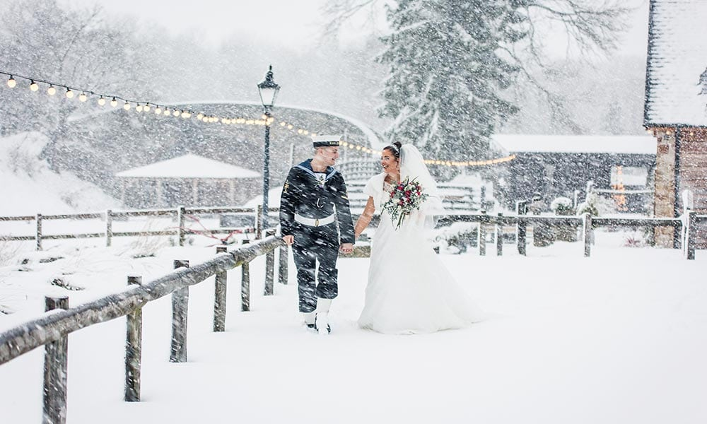 Image of bride and groom walking in the snow