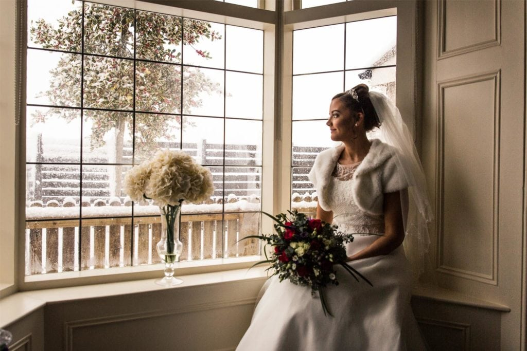 Bride sat next to a snowy window