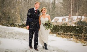 Bride and Groom walking through the snow