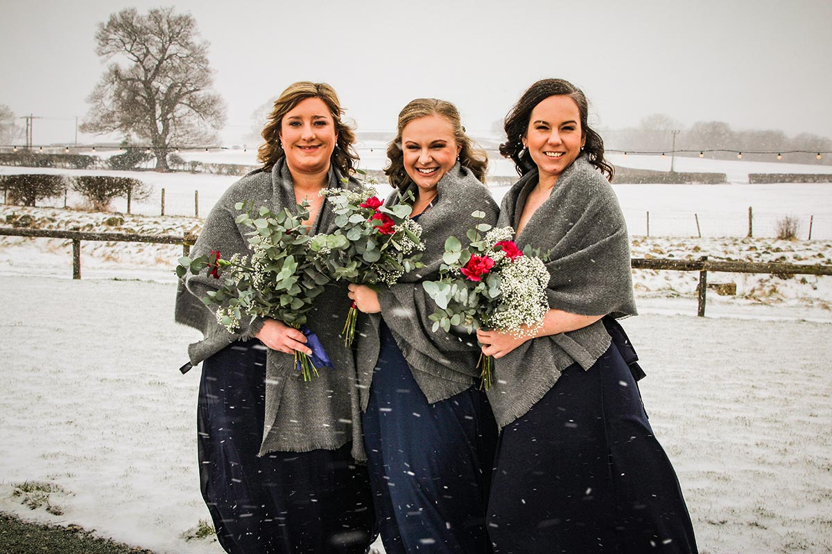 Bridesmaids stood in the snow
