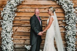 Bride and groom under an arch of flowers