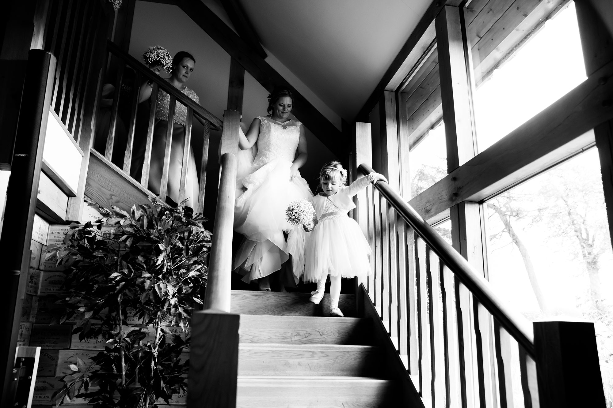 bride-to-be Jane and her bridesmaids walking down the staircase in the dining hall at Tower Hill Barns North Wales