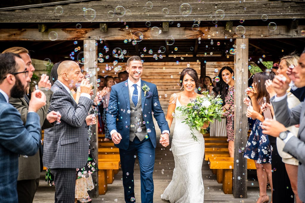 Summer outdoor ceremony at Tower Hill Barns with bubbles as confetti