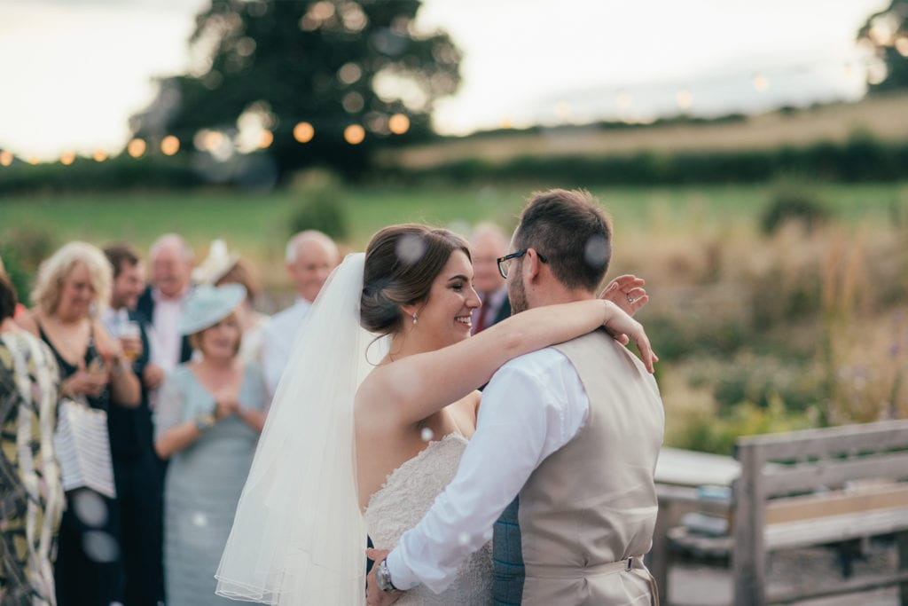 Newlywed couple have their first dance outdoor on the terrace during their summer wedding at Tower Hill Barns