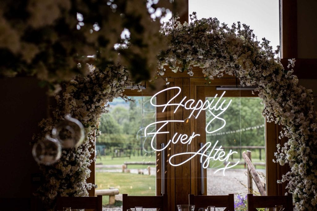 wedding breakfast setup at Tower Hill Barns with neon 'happily ever after' sign