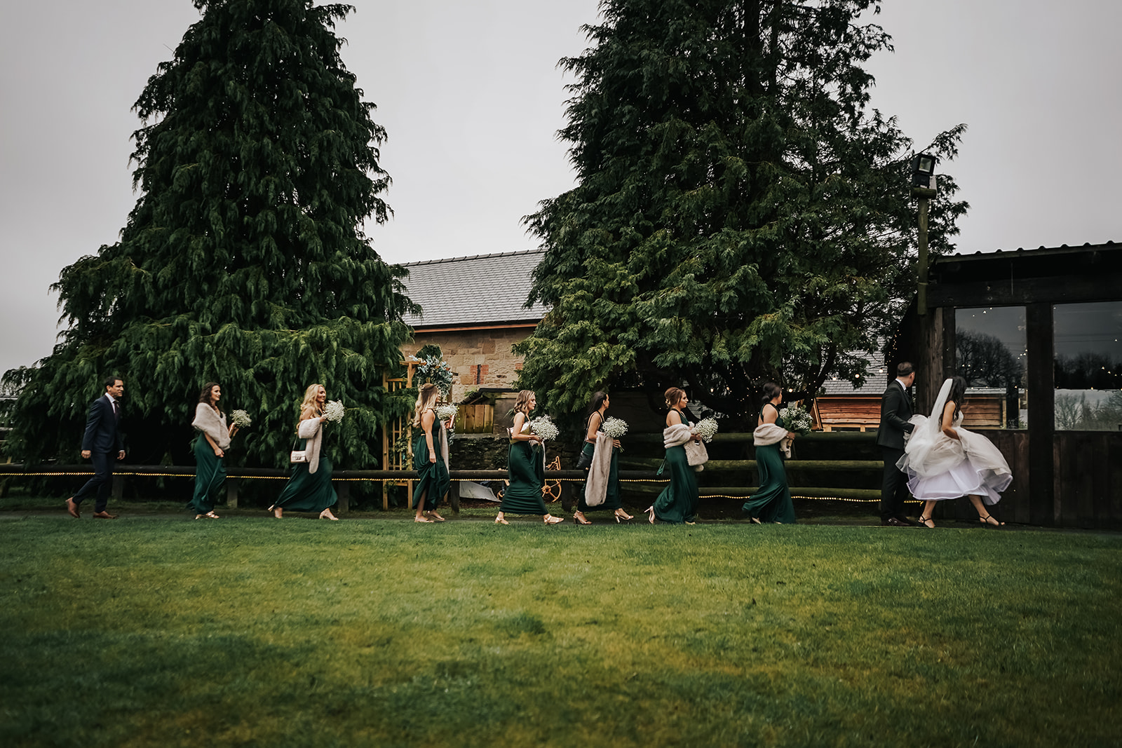 Winter wedding bridal party en route to their indoor ceremony wearing forest green bridesmaid dresses
