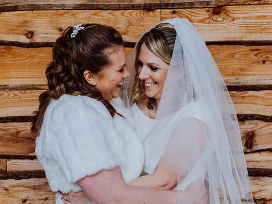 stunning same-sex wedding photo by Clara Cooper Photography of Wales first openly gay MP Hannah Blythin with wife Laura at Tower Hill Barns