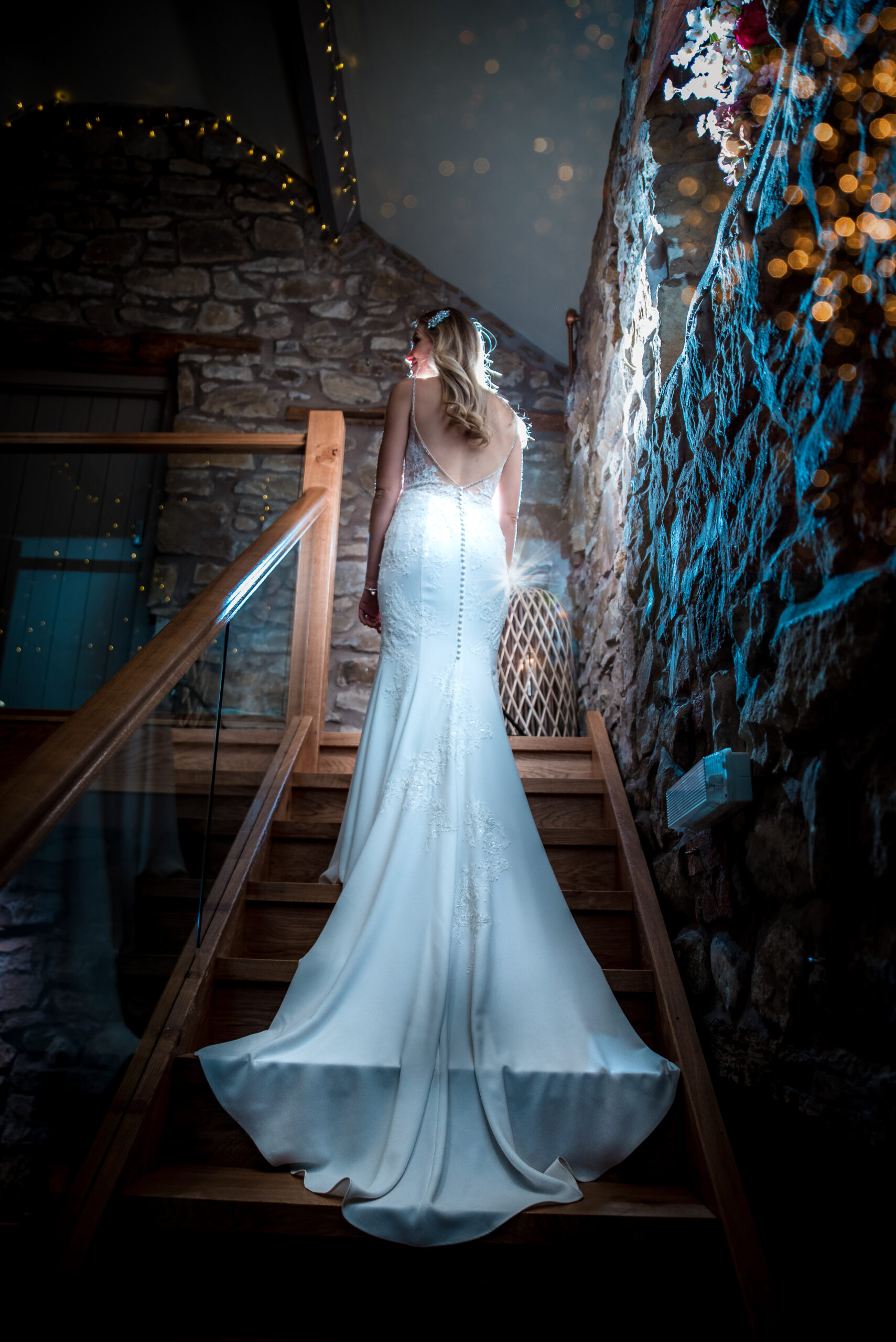 bride in white bridal gown with long train standing on the oak-framed stairs - indoor ceremony room - Tower Hill Barns - rustic lighting