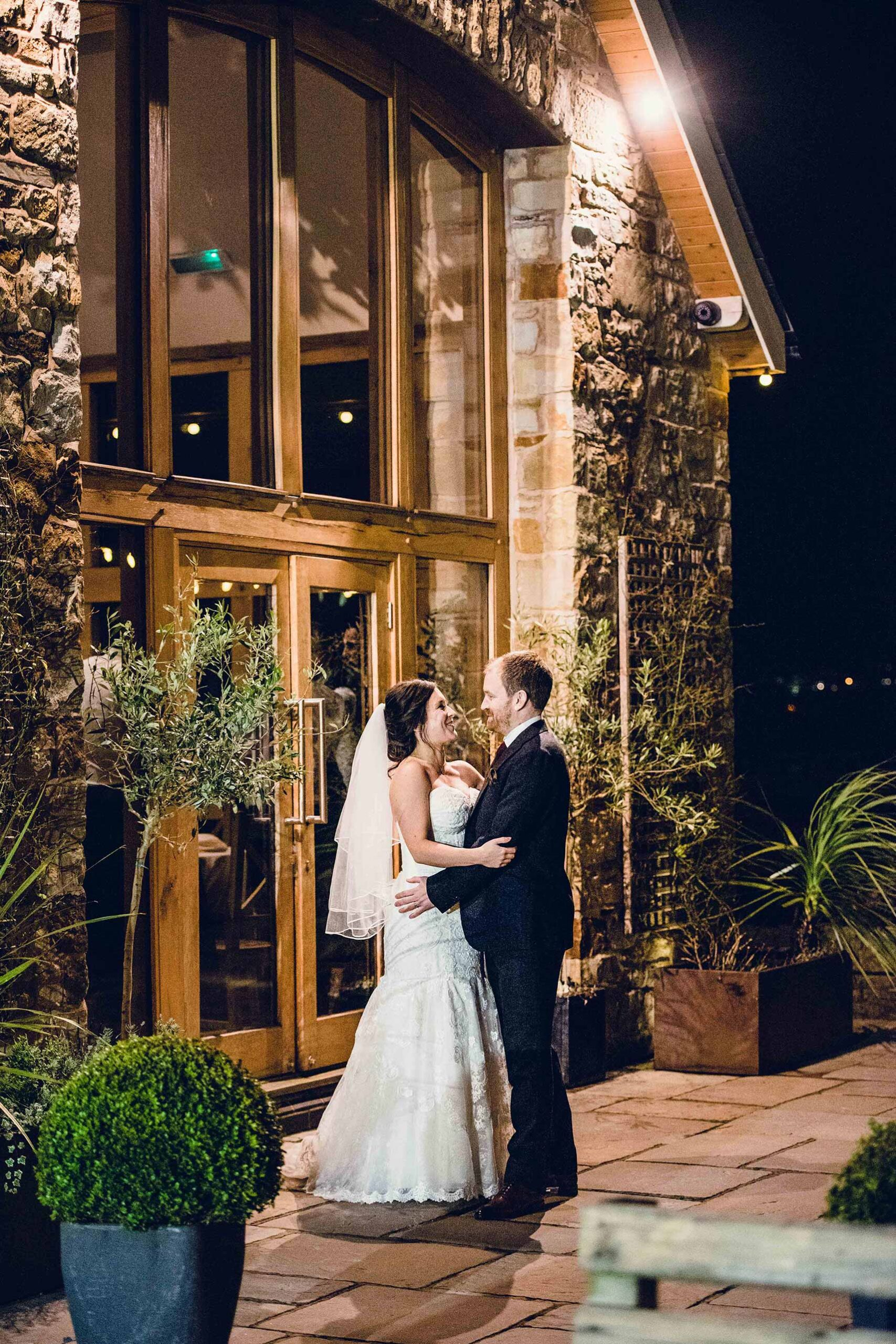 newlywed couple in front of the oak-framed Dining Hall - Tower Hill Barns - twilight