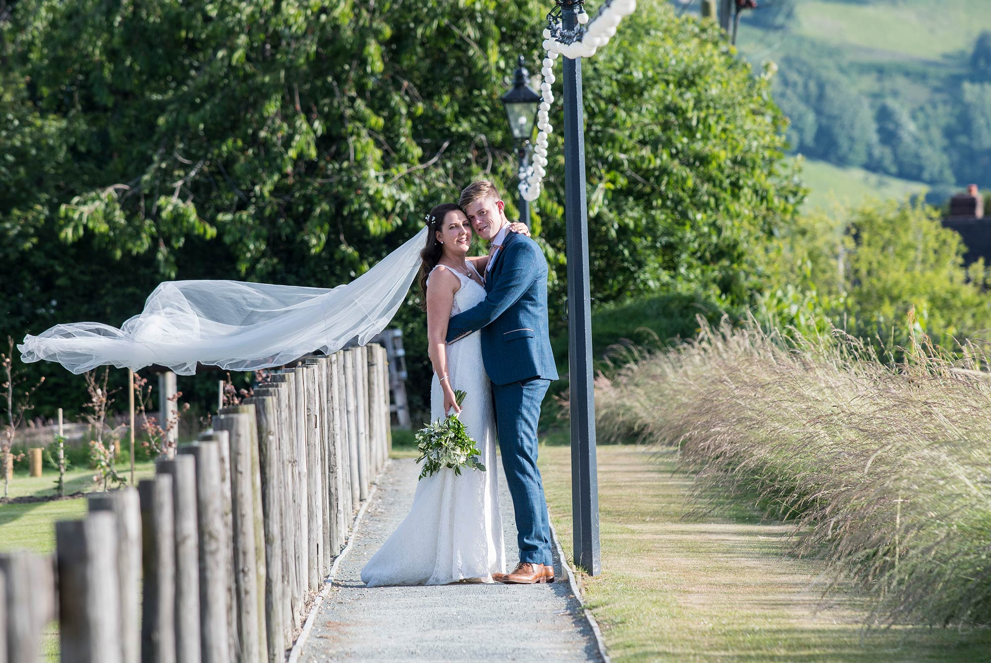 Cheshire newlyweds Claire and John posing for wedding portraits on the grounds of Tower Hill Barns | North Wales