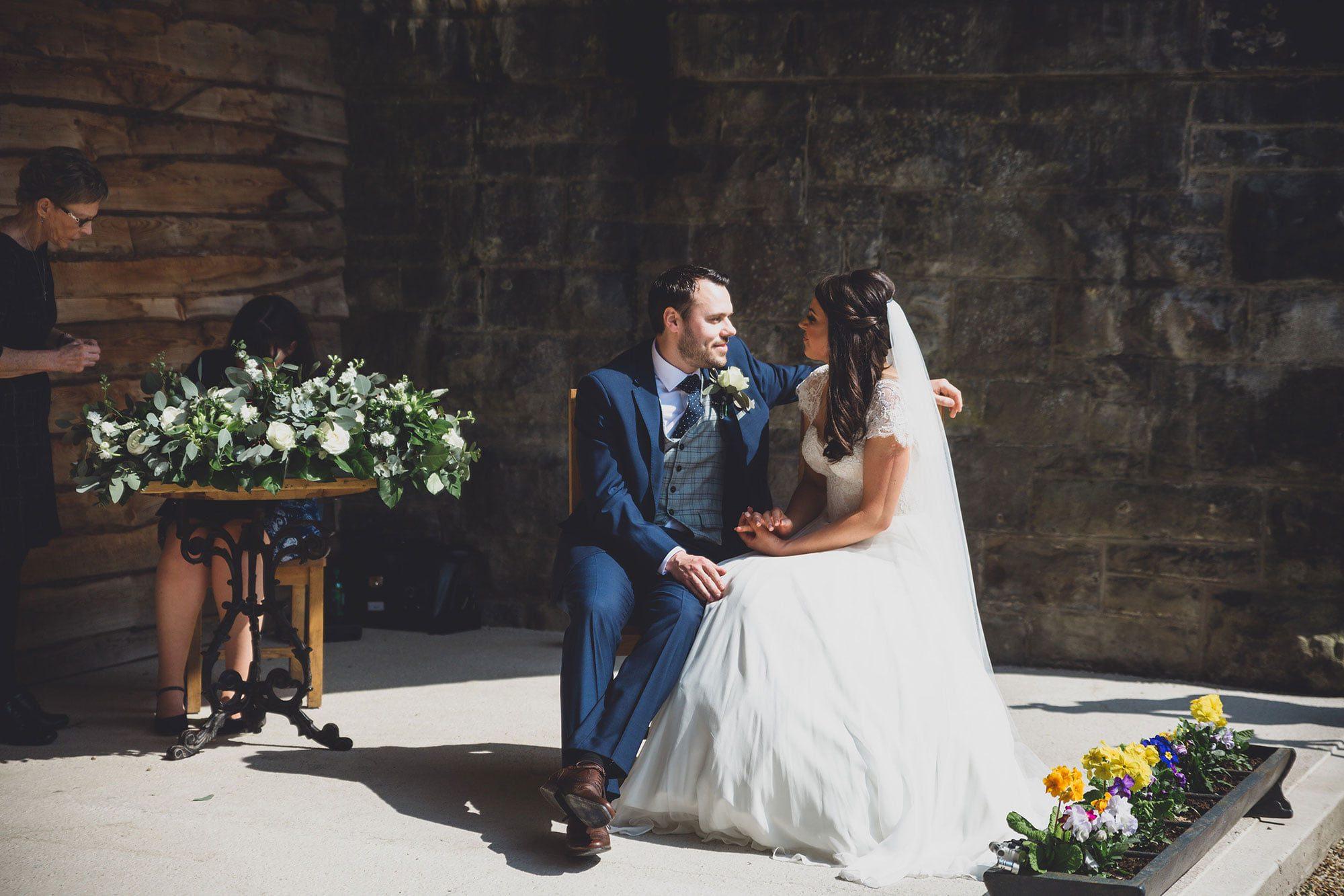 newlyweds Katherine & Nick sign their wedding register under the Old Railway Bridge; Tower Hill Barns