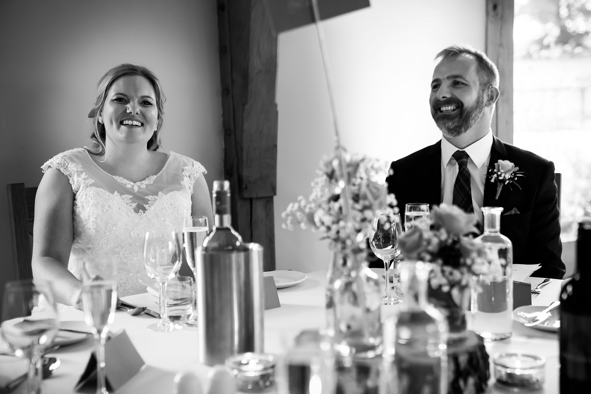 Jane & Conor sitting at their rustic top table during the wedding breakfast at Tower Hill Barns