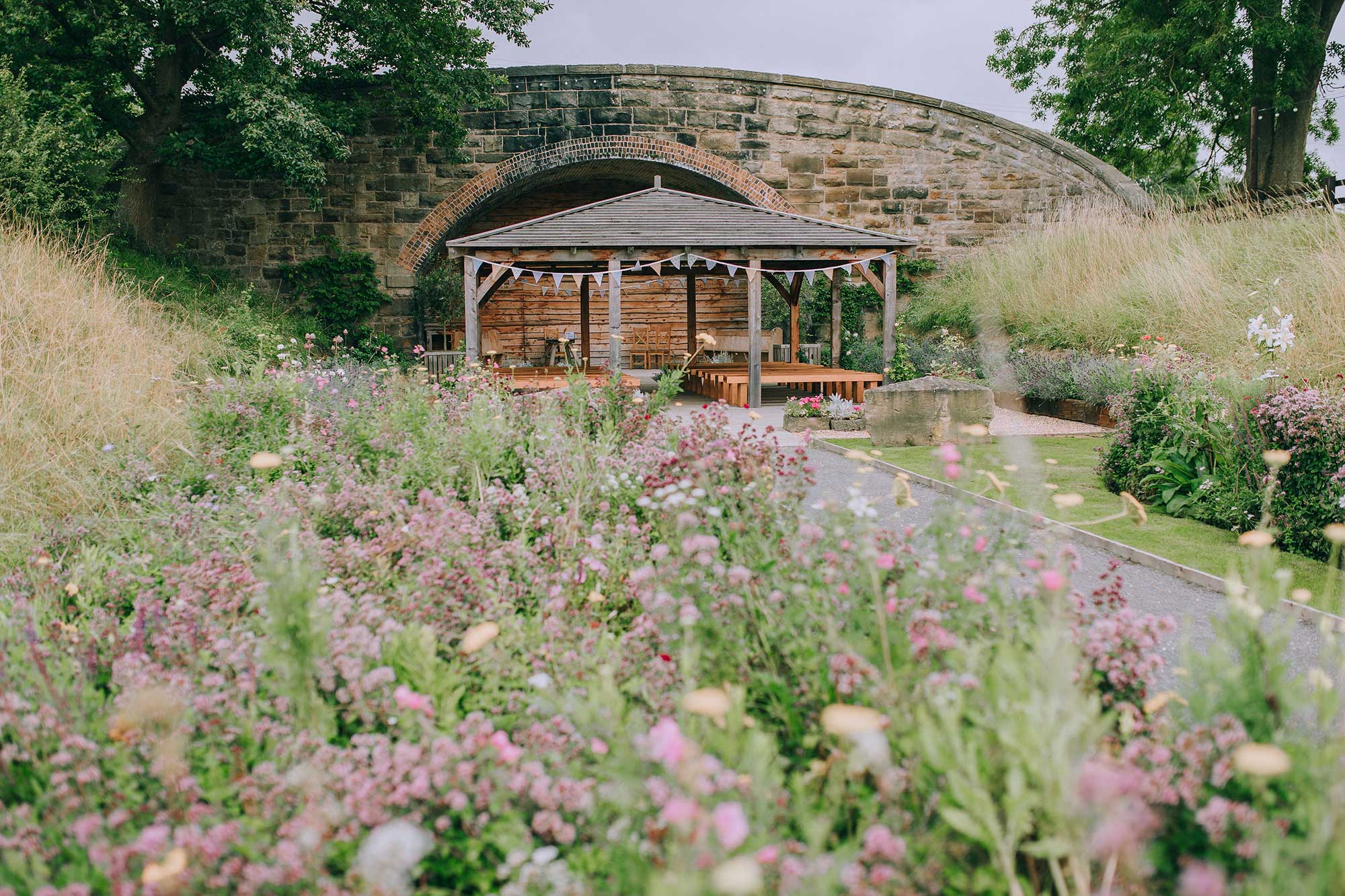 the outdoor ceremony area at Tower Hill Barns in full bloom with summer wildflowers lining the aisle and grounds; Nat Overthrow Photography