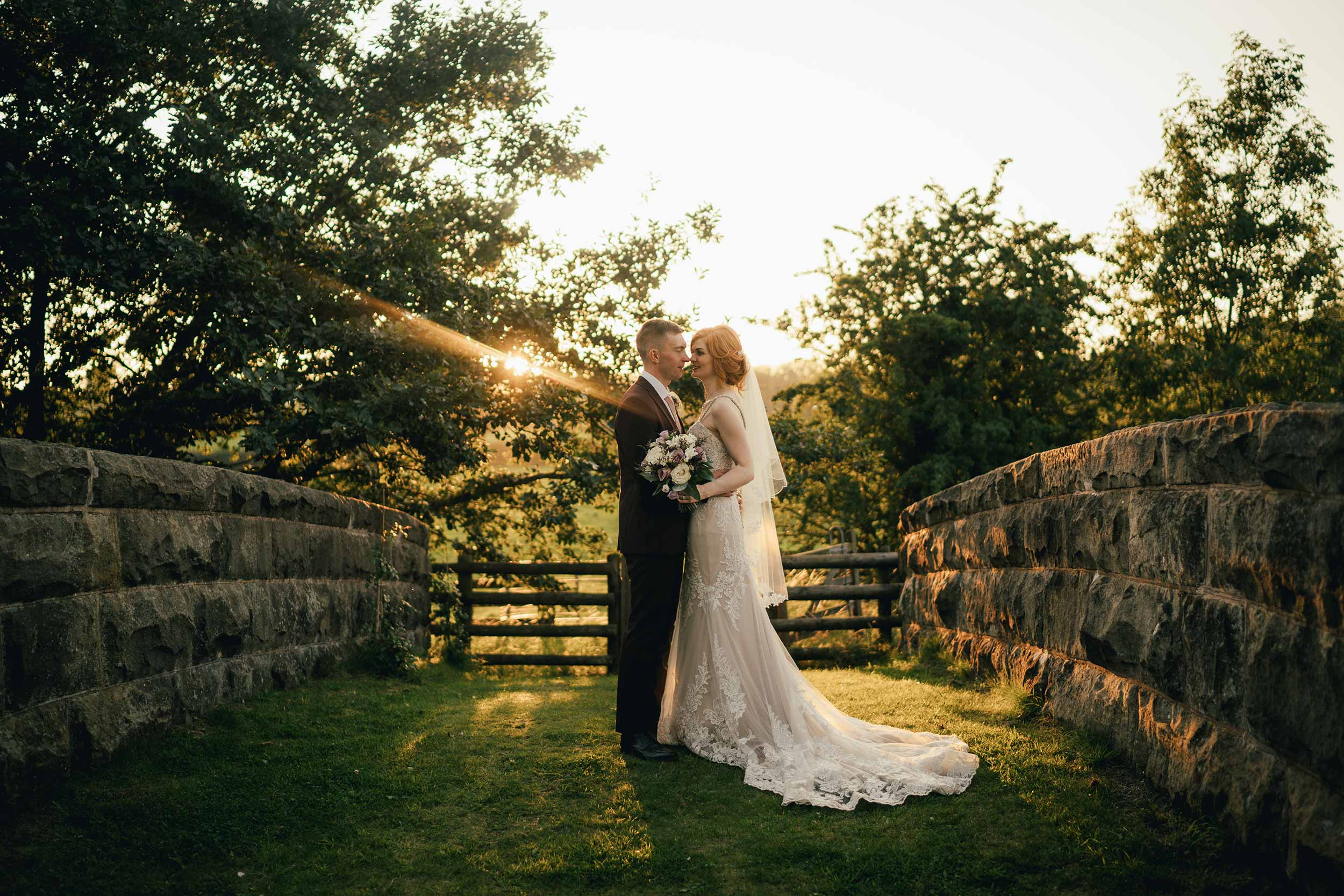 bride and groom in the countryside atop the Railway Bridge - Tower Hill Barns; North Wales - during golden hour; Lucy G Photography