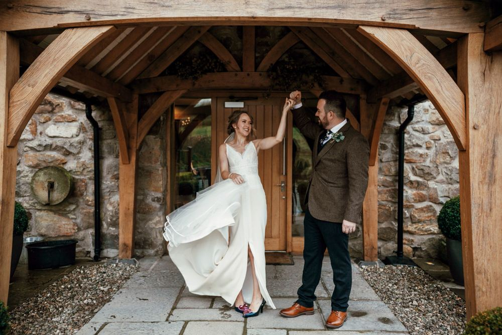 newlyweds dance under the barn arches - Tower Hill Barns - intimate autumn wedding
