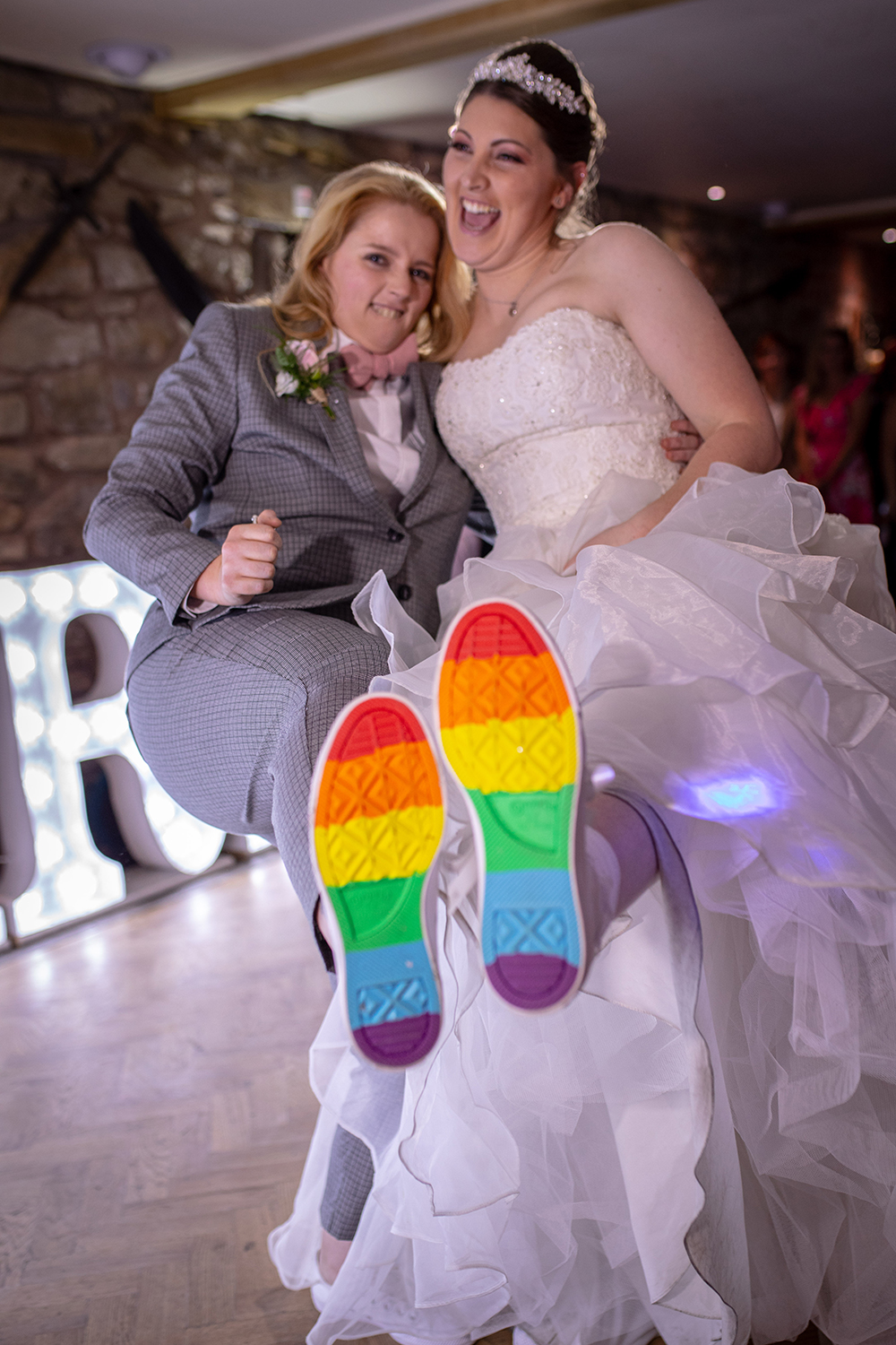 Woman wearing rainbow converse at her same-sex wedding, Tower Hill Barns; photography by Nathan Roberts